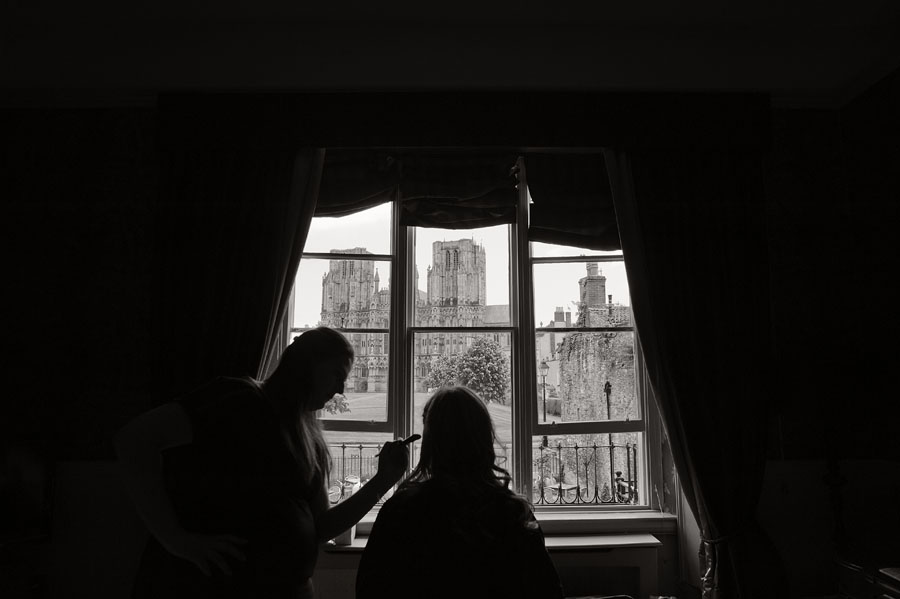 Bride and makeup artist silhouetted against a spectacular view