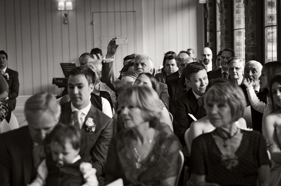 A guest takes a sneaky photo during the ceremony