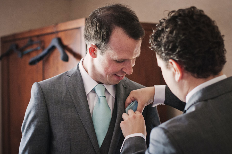 Best man helps groom with his lapel