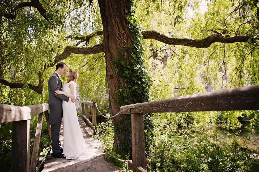 The newlyweds on a bridge in Wells' Bishop's Palace Gardens